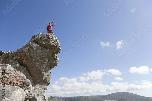 Male rock climber looking at view from on top of rock