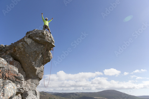 Male rock climber standing with arms outstretched on top of rock