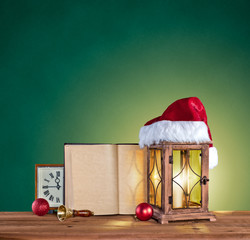 christmas hat, lantern, book and clock on a green vintage backgr