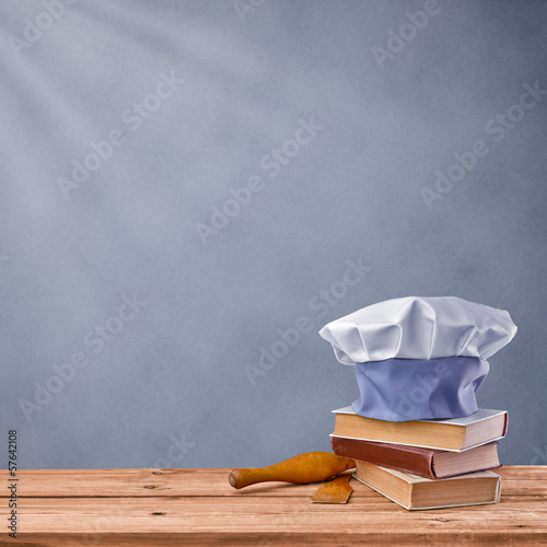 cap chef, cookbook and kitchenware on a grey vintage background