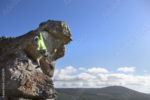 Male rock climber ascending rock face