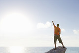 Male rock climber standing with arms raised on top of rock overlooking ocean