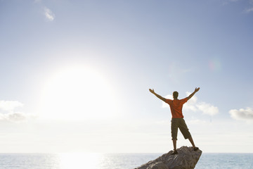 Male rock climber standing with arms outstretched on top of rock overlooking ocean