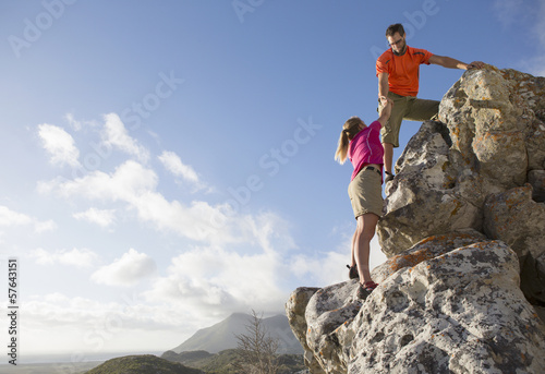 Male rock climber helping woman up rock face