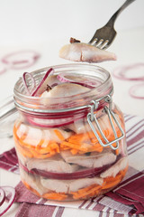 Jar of pickled herring, onion and carrots