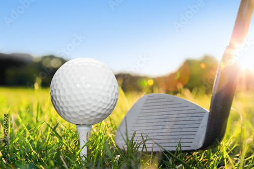 Golf ball on white tee and golf club preparing to shot.