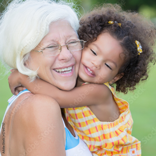 Grandmother hugs her hispanic granddaughter and laughs