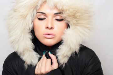 beautiful fashionable woman with fur. white fur hood. winter