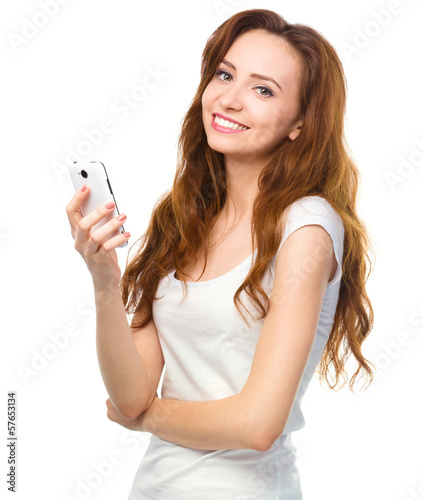 Young woman is typing sms message on her phone