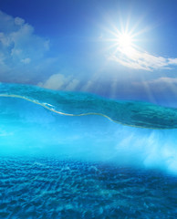 under clear sea water with sun shining sky and sand dune ground
