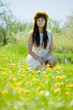 girl sitting outdoor in dandelion meadow