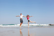 young loving couple joyfully jumps on a tropical beach
