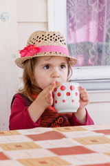 girl drinks milk from a cup