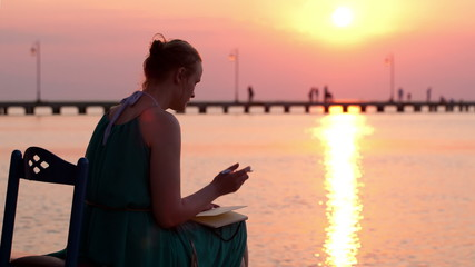 Young woman writing in her diary by the seashore