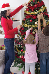 girl and boy helping her mother decorating the Christmas tree