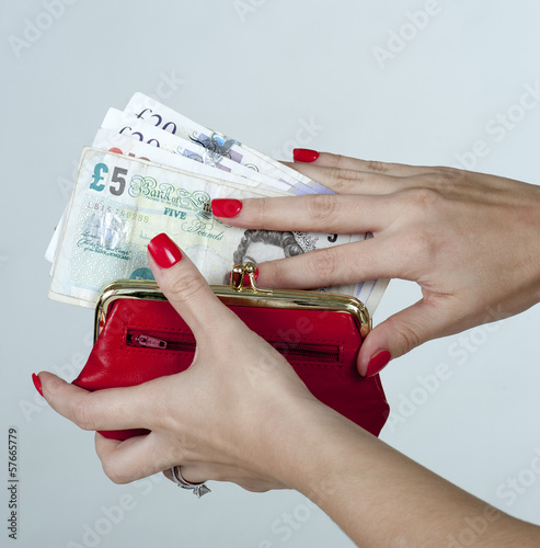 Woman putting pound notes in a red purse
