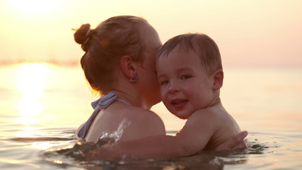 Son and mother embracing in the sea