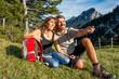 Paar macht Pause auf einer Wiese in den Bergen - 57669312