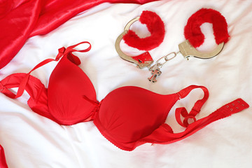 Red bra  and  handcuffs on bed
