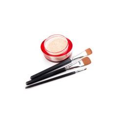 Three make-up brushes and powder isolated on white
