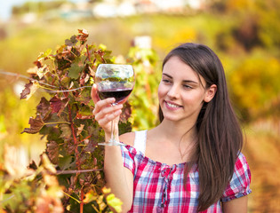 woman with glass of wine in the vineyard.