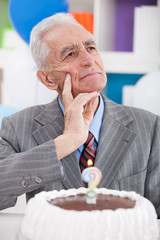 Thinking senior man with birthday cake