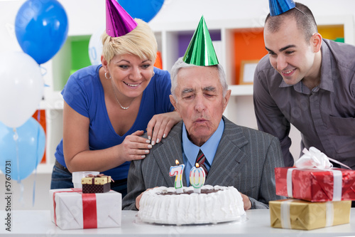Senior man blowing in  the candles on cake