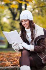 Woman reading in the autumn park