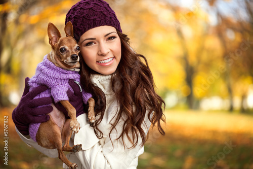 woman holding her puppy after in the park