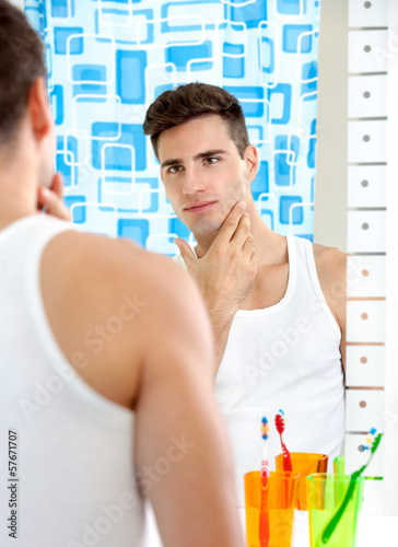 Man looks at himself in mirror