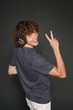 Happy male in headphones gesturing V sign over shoulder