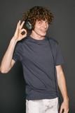 Happy male in headphones gesturing OK sign