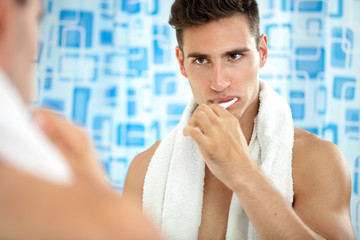 Man brushing teeth in front of mirror