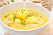 cauliflower soup with curry and cream in a bowl, close-up