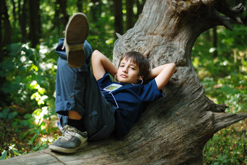 Boy with a gadget in the forest