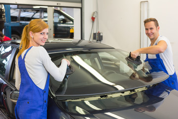Mechanics or glaziers install windshield on car