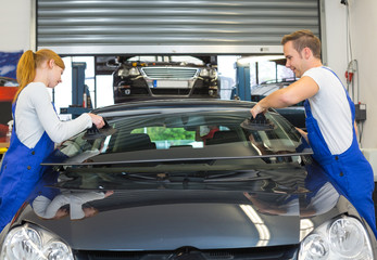 Glaziers replace windshield on car after stone-chipping