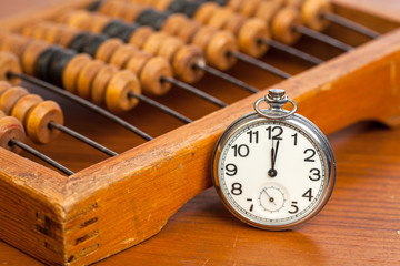 Pocket watch next to abacus
