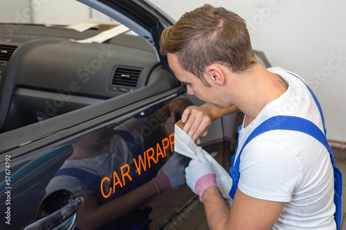 Car branding specialist puts logo with car wrapping film on auto - 57674792