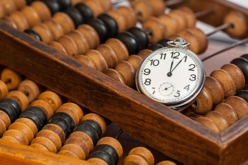 Pocket watch on abacus