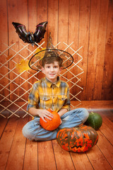 The boy sit with Helloween's carved pumpkin