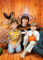 The father and two boys sit with pumpkins