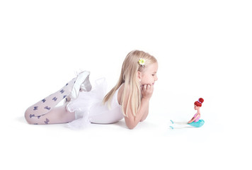 Sweet little ballerina posing with her doll.