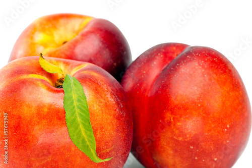 Ripe nectarine with a green leaf on a white background..