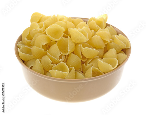 Small pasta shells in a tan bowl
