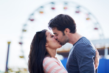 romantic couple kissing in front of santa monica ferris wheel