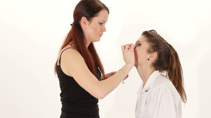 Make-up artist working with model in a studio