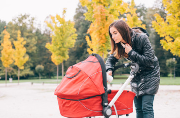 Young woman feeding baby milk in stroller