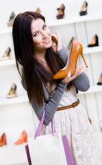 Half-length portrait of woman handing brown leather pump