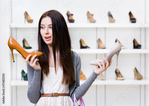 Woman keeps two high heeled shoes in the shopping mall